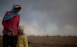 A Mongolian ethnic minority farmer is seen with her child in a farm in Kunlun Qi in the Inner Mongolia Autonomous Region of China on 23 April 2011. Inner Mongolia, China's third largest province, is fighting severe desertification, much like the provinces of Xinjiang, Gansu, Qinghai, Ningxia, Shaanxi, Heilongjiang and Hebei. Over-grazing, logging, expanding farms and population pressure, along with droughts have steadily turned once fertile grasslands into sandy plains. China has adopted measures to stop the land degradation such as reforestation, resettling nomadic Mongolians from grasslands to urban areas and restricting grazing areas. Tree planting has become a key government effort to combat desertification and supporting the government's reforestation endeavors are numerous non-governmental organizations (NGOs), such as Shanghai Roots & Shoots. The NGO launched the Million Tree Project in 2007 in Kulun Qi with aims to plant its first million trees by 2014 to hinder the expanding desert. To-date, they have planted more than 600,000 trees.