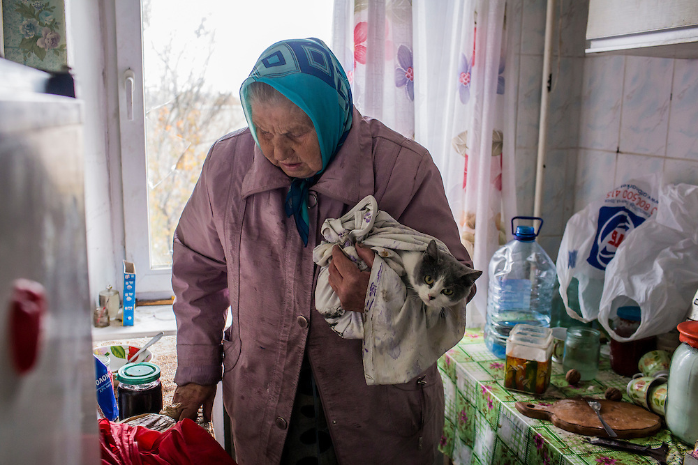 Nadezda Panasyk, 75, holds her cat Pushok (Fluffy) in her apartment in the Kievsky district where she lives on Friday, October 17, 2014 in Donetsk, Ukraine. Her building is used by fighters for the Donetsk People's Republic to coordinate efforts to gain control of the Donetsk airport, one of the most heavily contested ongoing battles of the war in Eastern Ukraine. Photo by Brendan Hoffman, Freelance