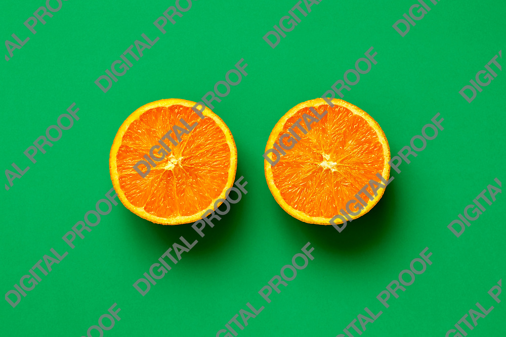 Orange fruit. Orange half fruit sliced isolate on green background seen from above flatlay style, close up.