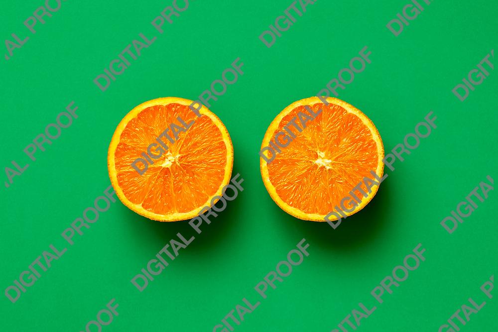 Orange fruit. Orange half fruit sliced isolate on green background seen from above flatlay style, close up.