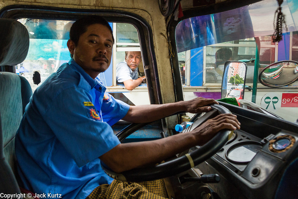 19 JUNE 2013 - YANGON, MYANMAR: A passenger stairs out the window of a Yangon bus as another bus passes him. Yangon buses are generally overcrowded and in poor repair but as the economy improves newer, but still used, Japanese and Korean buses are being imported. Hundreds of bus routes criss-cross Yangon, providing the cheapest way of getting around the city. Most fares are less than the equivalent of .20¢ US.   PHOTO BY JACK KURTZ