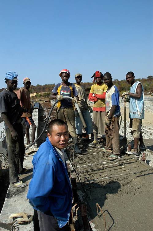 Chinese contractors and Angolan laborers rebuilding bridges along the Luena - Lucusse road. Infrastructure in large parts of the country was destroyed during the long years of war. As thousands of landmines are cleared along roads and bridges, the Angolan government is implementing a vast reconstruction program, much of it done by Chinese contractors, throughout the country..Canaje, Moxico Province, Angola. 23/07/2009..Photo © J.B. Russell
