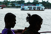 "17 JUNE 2013 - YANGON, MYANMAR: Passengers on the Yangon-Dala Ferry are silhouetted by the late afternoon sun as a ferry boat goes up the Yangon River. The ferry to Dala opposite Yangon on the Yangon River is the main form of transportation across the river. Every day the ferry moves tens of thousands of people across the river. Many working class Burmese live in Dala and work in Yangon. The ferry is also popular with tourists who want to experience the ""real"" Myanmar. The rides takes about 15 minutes. Burmese pay about the equivalent of .06¢ US for a ticket.  Foreigners pay about the equivalent of about $4.50 US for the same ticket.    PHOTO BY JACK KURTZ"