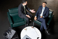 Two businessmen sitting at table talking elevated view