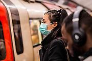 Double masking - Anti Coronavirus (Covid 19) defences, wearing inefectual masks on London Underground.