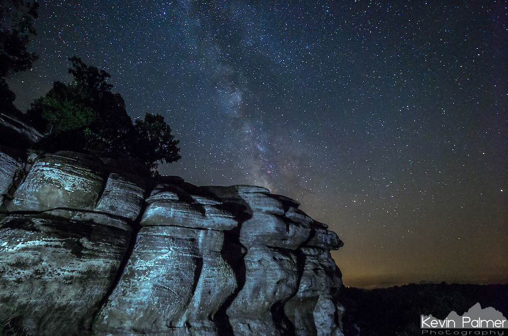 The milky way shines in the dark skies behind a cliff at Garden of the Gods, Illinois. I used a flashlight to light paint the cliffs from an angle, which created shadows and texture. The sky was a bit hazy which made the stars a little less clear.<br />
