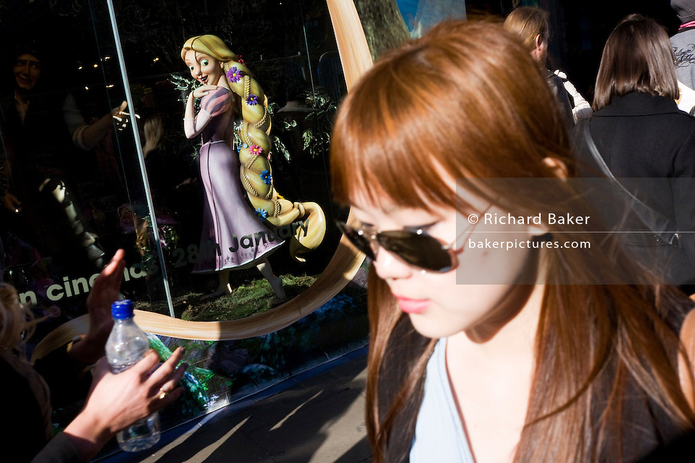 Disney character Rapunzel from their film Tangled stands looking at woman, exemplifying feminine beauty.