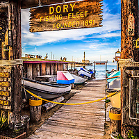 Photo of Newport Beach Dory Fishing Fleet Market entrance sign, dory boats, and Newport Pier on Balboa Peninsula in Orange County Southern California. Sign reads Dory Fishing Fleet Founded 1891. The Dory Fishing Fleet Market is a historical landmark where Dory fisherman bring in and sell the daily catch at the Dory Fish Market. Photo is high resolution.