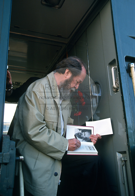 Russian Nobel prize novelist Alexander Solzhenitsyn signs a copy of his book after arriving by train returning to his homeland June 5, 1995 in Khabarovsk, Russia. Solzhenitsyn was expelled from the Soviet Union in 1974 but returned after the fall of the Soviet Union.