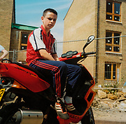 Boy sitting on a moped in a newly built housing complex
