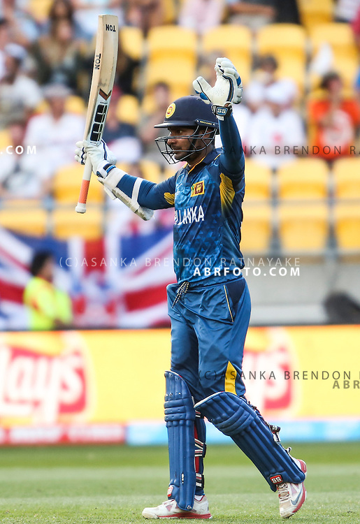 Kumar Sangakkara raises his arms and bat in celebration after reaching his century during the 2015 ICC Cricket World Cup Pool A group match between England Vs Sri Lanka at the Wellington Regional Stadium, Wellington, New Zealand.