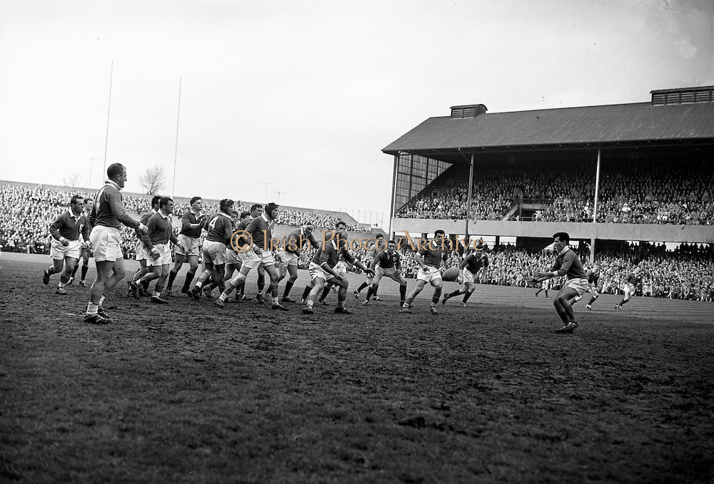 French forward, A Roques, centre left, passes the ball to P Danos, French scrum half, on right, with the whole forward lines of both teams breaking away from the scrum, ..Irish Rugby Football Union, Ireland v France, Five Nations, Landsdowne Road, Dublin, Ireland, Saturday 18th April, 1959,.18.4.1959, 4.18.1959,..Referee- D G Walters, Welsh Rugby Union, ..Score- Ireland 9 - 5 France, ..Irish Team, ..N J Henderson, Wearing number 15 Irish jersey, Full Back, N.I.F.C, Rugby Football Club, Belfast, Northern Ireland, ..A J O'Reilly, Wearing number 14 Irish jersey, Right Wing, Old Belvedere Rugby Football Club, Dublin, Ireland, and, Leicester Rugby Football Club, Leicester, England, ..M K Flynn, Wearing number 13 Irish jersey, Right Centre, Wanderers Rugby Football Club, Dublin, Ireland, ..D Hewitt, Wearing number 12 Irish jersey, Left centre, Queens University Rugby Football Club, Belfast, Northern Ireland,..N H Brophy, Wearing number 11 Irish jersey, Left wing, University College Dublin Rugby Football Club, Dublin, Ireland, ..M A F English, Wearing number 10 Irish jersey, Outside Half, Bohemians Rugby Football Club, Limerick, Ireland,..A A Mulligan, Wearing number 9 Irish jersey, Scrum Half, London Irish Rugby Football Club, Surrey, England, ..B G Wood, Wearing number 1 Irish jersey, Forward, Garryowen Rugby Football Club, Limerick, Ireland, ..A R Dawson, Wearing number 2 Irish jersey, Captain of the Irish team, Forward, Wanderers Rugby Football Club, Dublin, Ireland, ..S Millar, Wearing number 3 Irish jersey, Forward, Ballymena Rugby Football Club, Antrim, Northern Ireland,..W A Mulcahy, Wearing number 4 Irish jersey, Forward, University College Dublin Rugby Football Club, Dublin, Ireland, ..M G Culliton, Wearing number 5 Irish jersey, Forward, Wanderers Rugby Football Club, Dublin, Ireland, ..N Murphy, Wearing number 6 Irish jersey, Forward, Cork Constitution Rugby Football Club, Cork, Ireland,..P J A O' Sullivan, Wearing  Number 7 Irish jersey, Forward, Galwegians Ru