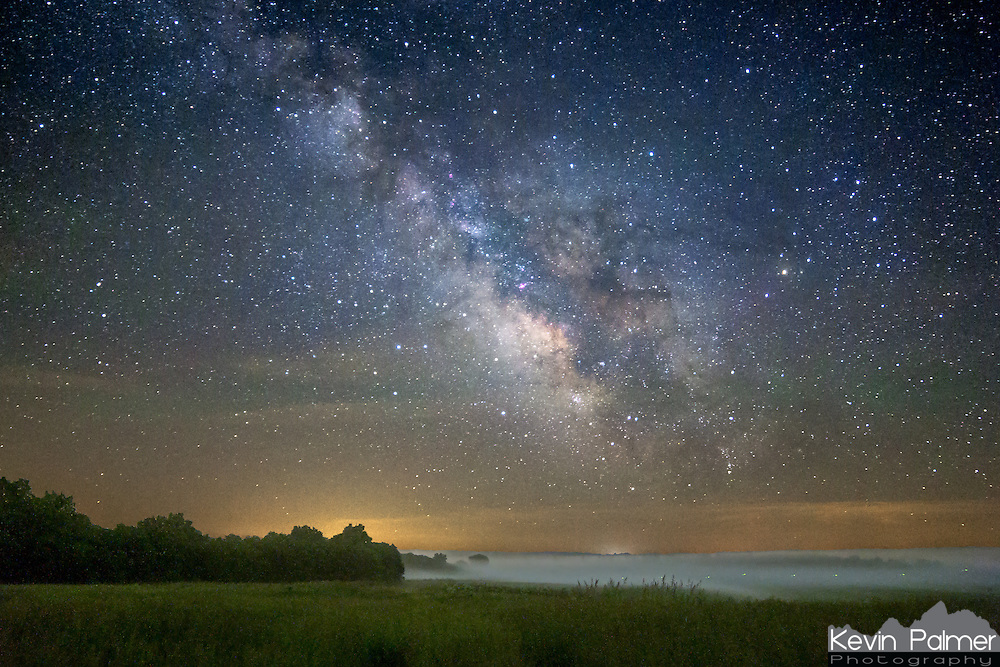 Fog moves around a field as the milky way galaxy rises higher in the sky. This was taken near the Iowa and Missouri border in some of the darkest skies in the entire midwest. The only evidence of light pollution was in the yellow clouds lit up by a small town 15 miles away. The green dots on the bottom right are from a firefly fleeing the scene.