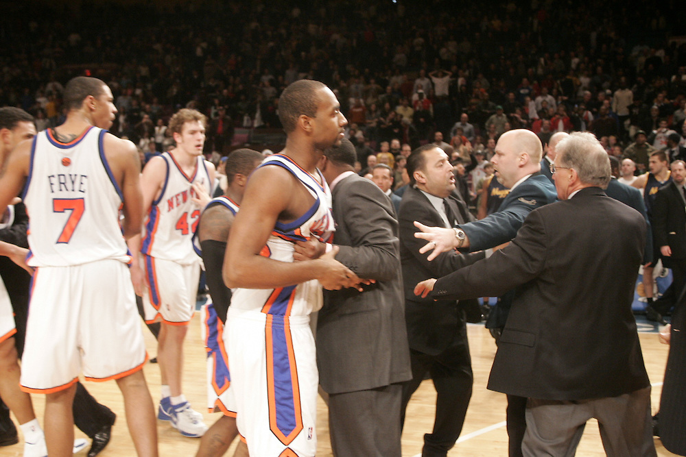 Members of the New York Knicks are restrained by security during a fight with the Denver Nuggets at Madison Square Garden, New York on Saturday  16 December 2006. (Andrew Gombert for The New York Times)