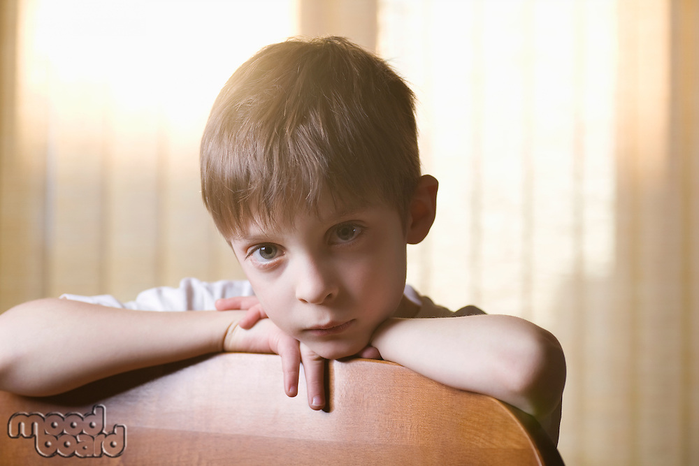 Boy sits looking at camera leaning on chair back