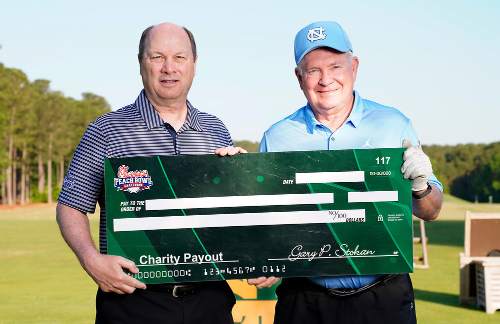 Peach Bowl, Inc. CEO & President Gary Stokan presents North Carolina head football coach Mack Brown a check for his charity after the Chick-fil-A Peach Bowl Challenge at the Ritz Carlton Reynolds, Lake Oconee, on Tuesday, April 30, 2019, in Greensboro, GA. (Paul Abell via Abell Images for Chick-fil-A Peach Bowl Challenge)