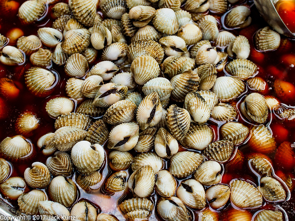 """18 MAY 2017 - BANGKOK, THAILAND: Cockles for sale at a street food stall in Bangkok's Chinatown. City officials in Bangkok have taken steps to rein in street food vendors. The steps were originally reported as a """"ban"""" on street food, but after an uproar in local and international news outlets, city officials said street food vendors wouldn't be banned but would be regulated, undergo health inspections and be restricted to certain hours on major streets. On Yaowarat Road, in the heart of Bangkok's touristy Chinatown, the city has closed some traffic lanes to facilitate the vendors. But in other parts of the city, the vendors have been moved off of major streets and sidewalks.      PHOTO BY JACK KURTZ"""