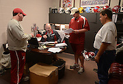 Equipment managers work in the Mal Moore Athletic Facility to get the University of Alabama football team ready for the trip to Baton Rouge to face LSU.  Equipment manager Jeff Springer, seated, gives instruction to student managers Thomas Hall, left and Michael Neese, center, while truck driver Jack Vickers listens.  Photo by Gary Cosby Jr.