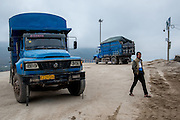Trucks wait to be loaded with dredged sand in the town of Simaogangzhen, Yunan, China. The dredged sand is sold locally and to large scale construction sites in nearby major cities such as Kunming and Jinhong.