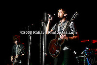 Kings of Leon performing at Madison Square Garden on January 29, 2009. ..Matthew Followill - wearing black leather jacket (lead guitar/backup vocals)..Caleb Followill -  beard, wearing a grey t-shirt and black vest. (lead singer/rhythm guitar. Nathan Followill (drums/backup vocals)..