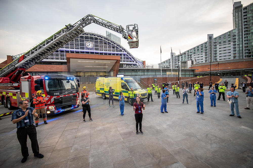 """© Licensed to London News Pictures. 23/04/2020. Manchester, UK. Emergency services show support for carers at a """" Clap for our Carers """" event outside the Nightingale NW Hospital in Manchester . The National Health Service has built a 648 bed field hospital for the treatment of Covid-19 patients , at the historical railway station terminus which now forms the main hall of the Manchester Central Convention Centre . The facility treats patients from across the North West of England , providing them with general medical care and oxygen therapy after discharge from Intensive Care Units . Photo credit: Joel Goodman/LNP"""