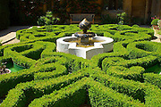 An intricate, curvacious box parterre with central Islamic style ceramic-tiled fountain. The feathery green heads of exotic papyrus plants rise from pots at the four corners of the garden.<br />