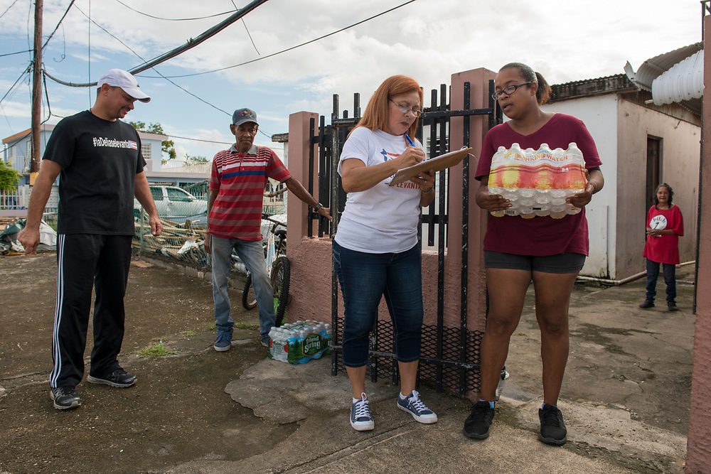 Toa Baja, PR, November 10, 2017--Inamarys Carreras and Eric Rossner, left, are part of a team of faculty and staff of Escuela Delia Cabán who continue to distribute water and emergency relief in Tao Baja, PR neighborhoods still without power and water 50 days after Hurricane Maria.  Escuela Delia Cabán has served as a distribution point for the Puerto Rico Recovery Fund's emergency relief efforts since it was established days after the storm hit September 20, 2017.  Photo by Lori Waselchuk/BRAF