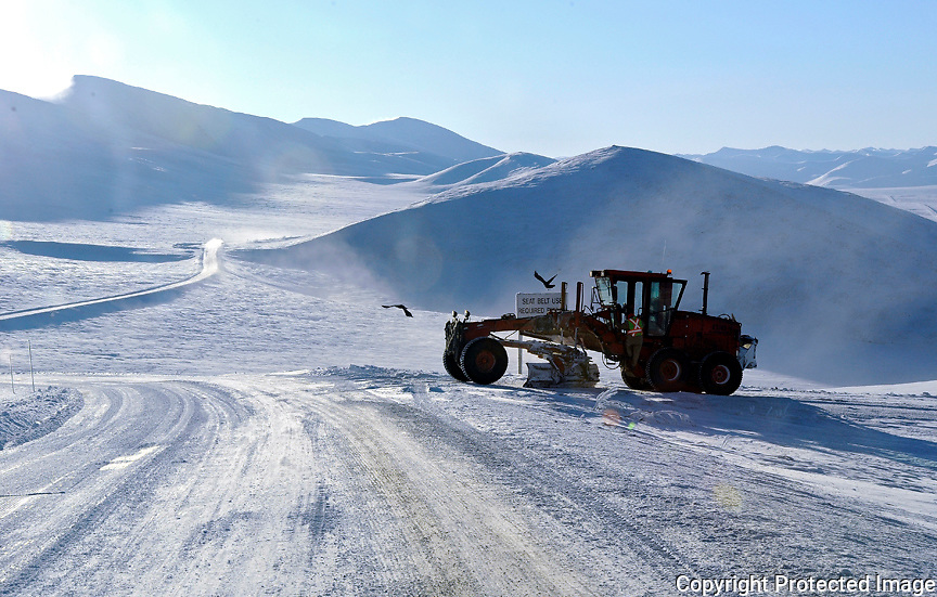 Ian Stewart/Yukon News<br /> A grader waits in Hurricane Alley, where winds regularly exceed 100 kph, causing snow to drift over the Dempster Highway.