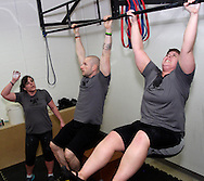 (from left) Sarah Collinsworth of Dayton, owner Jason Hoskins of Dayton and Sarah Stewart of Kettering during a workout of the day session at Vigor Crossfit in Moraine, Wednesday, January 25, 2012.