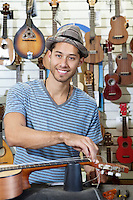 Portrait of happy man restringing guitar in music store