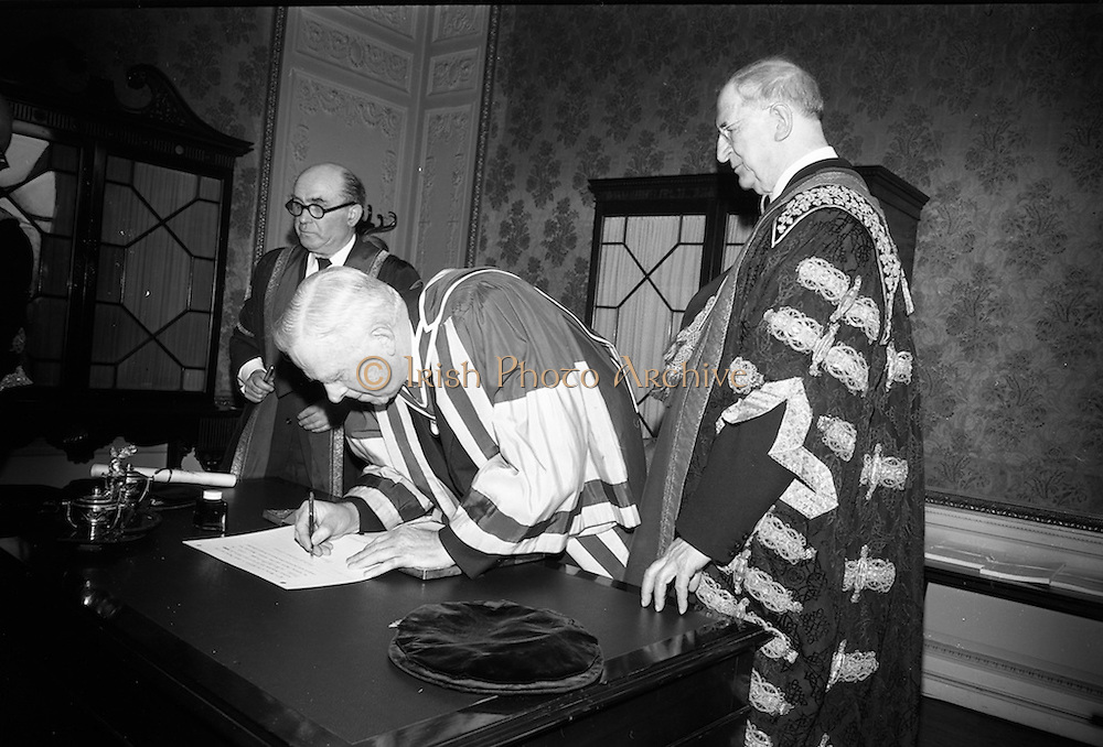 23/04/1964<br /> 04/23/1964<br /> 23 April 1964<br /> Honorary Degrees conferred at the National University of Ireland, Iveagh House, Dublin. <br /> Picture shows Dr. Seamus (James) Ryan (Degree D.Econ.Sc.), Minister for Finance, who received the degree of D.Econ.Sc. signing the register after the ceremony watched by President Eamon de Valera (right), Chancellor of N.U.I. and Dr. Seamus Wilmot, Registar of the University.