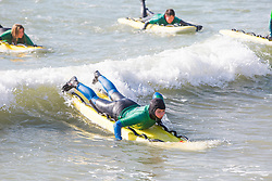© Licensed to London News Pictures. 24/02/2018. Brighton, UK. Members of the Brighton Surf Life Saving club brave the cold temperatures to take part in their weekly training in the Brighton and Hove sea. Photo credit: Hugo Michiels/LNP