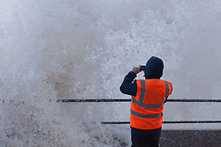 © Licensed to London News Pictures. 03/01/2014.New Brighton, UK . A man photographs the storm surge as high tide arrives on the River Mersey.  Photo credit : Andrew Dawson/LNP