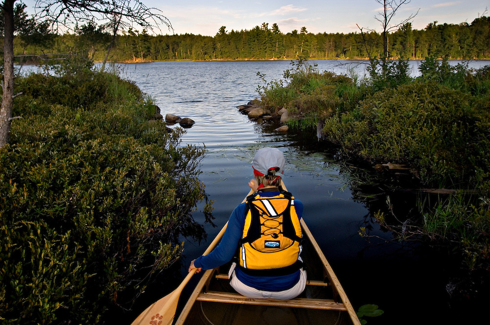 Paddling a narrow backwater near Lilvis Lake in Sylvania Wilderness Area of the Ottawa National Forest near Watersmeet Michigan.