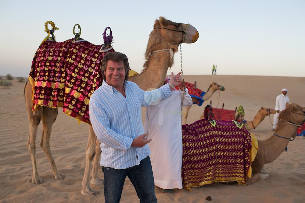 Andy Borg (vorne) mit Kamelen und Kamelfuehrern im Wuestencamp bei Dubai. Der Musikantenstadl hat hier aufgeschlagen, um am Abend ein Konzert zu geben.