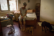 EVA RUPPEL sits on her bed, in her rural property near Kandy, Sri Lanka, while watching two street dogs she rescued, on Wednesday, February 21, 2018. Ruppel does not cage the approximate 170 rescued dogs that share her home, allowing them freedom to roam and interact in small packs in multiple pens throughout her property, as well as inside her home. Ruppel created Tikiri Trust, with the financial assistance of her father, to rescue and rehome Sri Lanka's street dogs.<br /> <br /> It is impossible to visit Sri Lanka without seeing street dogs in nearly every public space, near hotels, guest houses and restaurants, schools, offices, markets, hospitals, police stations, bus terminals, railway stations, temples, etc. These dogs do not have their own homes, but they are usually highly tolerated and are typically fed collectively by people in a particular area.<br /> <br /> According to the NGO, Kandy Association for Community Protection through Animal Welfare (KACPAW), 100 unsterilized dogs will give rise to 3,000 dogs in one year. The Sri Lankan government, as well as several NGOs, work to spay/neuter animals, but there is need to educate the public and maintain funds to stay on top of their efforts.<br /> <br /> Eva Ruppel left Germany for a three-month visit to Sri Lanka, which included time in a Buddhist meditation retreat, and she remains in this island nation 37 years later.<br /> <br /> While married, Ruppel&rsquo;s husband asked that the couple keep only three dogs in their home at any one time, and she respected his wishes. This 60-something year old lost her husband to a ruptured brain blood vessel in 1995 when he was 51 years old, after nine years of marriage. After his death, she began rescuing more and more animals and she now lives with 170 dogs, plus a dozen or so cats.<br /> <br /> With the support of her father, she started Tikiri Trust. Her father passed away in 2011, and he left her an inheritance, which she continues to use to support her cause. <br /> <br /> Ruppel, who is fluent in German, English and Sinhala, said that sh