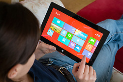 Woman using Windows 8 on a Microsoft Surface rt tablet computer