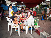 "14 MAY 2015 - BANGKOK, THAILAND:  Performers put on their makeup before going on stage at the Pek Leng Keng Mangkorn Khiew Shrine in the Khlong Toey slum in Bangkok. Chinese opera was once very popular in Thailand, where it is called ""Ngiew."" It is usually performed in the Teochew language. Millions of Chinese emigrated to Thailand (then Siam) in the 18th and 19th centuries and brought their culture with them. Recently the popularity of ngiew has faded as people turn to performances of opera on DVD or movies. There are still as many 30 Chinese opera troupes left in Bangkok and its environs. They are especially busy during Chinese New Year and Chinese holiday when they travel from Chinese temple to Chinese temple performing on stages they put up in streets near the temple, sometimes sleeping on hammocks they sling under their stage. Most of the Chinese operas from Bangkok travel to Malaysia for Ghost Month, leaving just a few to perform in Bangkok.      PHOTO BY JACK KURTZ"
