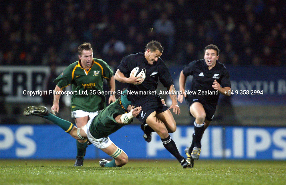 9 August 2003, International Rugby Union, Phillips Tri-Nations, All Blacks v South Africa, Carisbrook, Dunedin, New Zealand.<br />Carlos Spencer slips through the tackle from Victor Matfield. All Blacks won 19-11<br />Pic: Sandra Teddy/Photosport