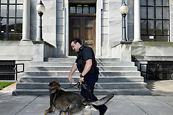 Norristown, PA., USA - May 24, 2016; K9 unit officer inspects the exterior at Montgomery County Court House in Norristown, PA. The courthouse is the location for the sexual assault trail of actor and comedian Bill Cosby.