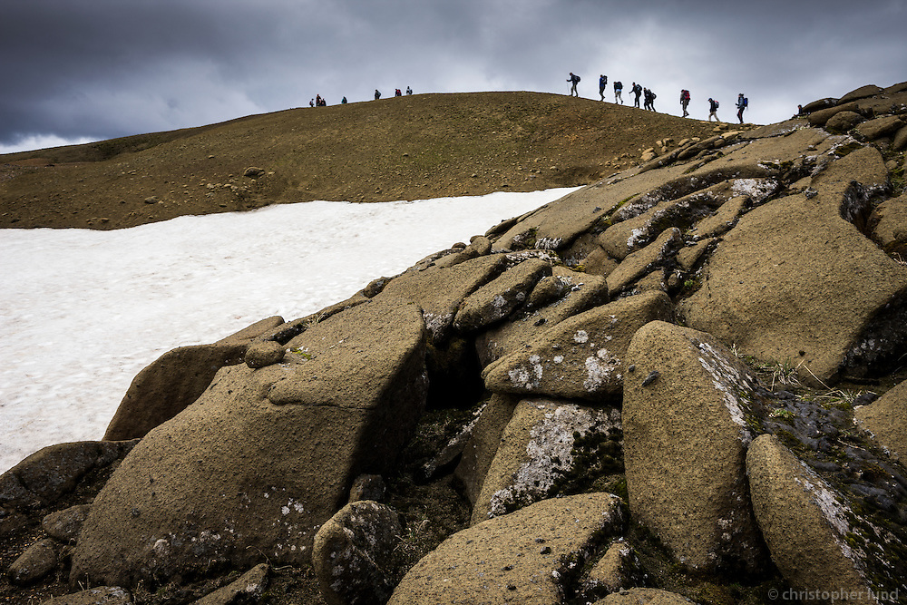 People hiking in Kerlingarfjöll mountain range, Interior of Iceland. Boulders with white and black moss in forground.