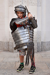 © Licensed to London News Pictures. 26/08/2017. London, UK. Cyrus Hopkinson, aged 6, from west London, tries on Roman armour as members of the Brittania re-enactment group put on Gladitorial Games in Guildhall Yard, the site of London's only Roman Amphitheatre.  The Gladiator Games will be entertaining crowds over the August Bank Holiday Weekend. Photo credit : Stephen Chung/LNP