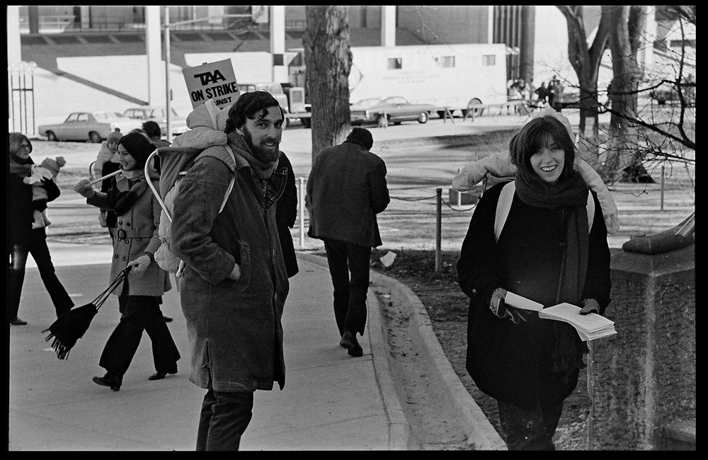 Madison, WI - March 1970. On March 15, 1970, the University of Wisconsin - Madison Teaching Assistants' Association voted to strike, and the campus was filled with picket lines as well as demonstrations of related and other issues. The strike lasted until early April, when the Association and University came to an agreement. A family with children in backpacks hands out leaflets.
