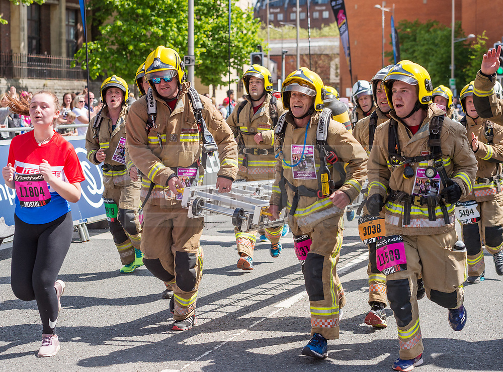© Licensed to London News Pictures. 13/05/2018. Bristol, UK. Simplyhealth Great Bristol 10k run. 13,000 runners are set to take part. Starting on Anchor Road near Bristol Cathedral, they'll be set off by 2018 Olympic Winter Medallist Dom Parsons, who took home bronze in the skeleton race this January. 30 firefighters (pictured) are running the Great Bristol 10k this weekend in full fire apparatus while carrying one of their ladders to raise money for three-year-old Daisy Bowyer, who has cerebral palsy and relies on the use of a walking frame and wheelchair. They hope to raise over £20,000 to pay for a private operation that would allow her to walk unaided. The group will run the 10k course with the six-metre long ladder and fire kit, weighing 30kg per firefighter. Photo credit: Simon Chapman/LNP