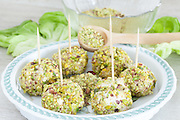 Italian gourmet recipe, balls of cheese and prosciutto in chopped pistachio.