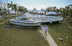 September 12, 2017 - Key Largo, Florida, U.S. - CHRIS MORGAN  inspects the large boats that beached onto the property she in stayed during Hurricane Irma's storm surge in Key Largo. (Credit Image: © Al Diaz/TNS via ZUMA Wire)