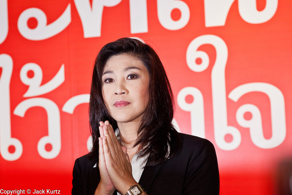 "03 JULY 2011 - BANGKOK, THAILAND:     YINGLUCK SHINAWATRA, the Prime Minister elect of Thailand, performs a ""wai"" or traditional Thai greeting before announcing her victory in the Thai elections Sunday night. If her election holds she will be the first woman elected Prime Minister of Thailand. Yingluck Shinawatra and the Pheu Thai Party scored a massive landslide win in the Thai election Sunday. Pheu That is estimated to have won more than 300 seats in Thailand 500 seat parliament, so they won an absolute majority and could govern without having to form a coalition with minor parties. Pheu Thai is the latest incarnation of deposed former Prime Minister Thaksin Shinawatra's political party. Yingluck is his youngest sister. Many observers expect legal challenges to the Pheu Thai victory and the election does not completely resolve Thailand's difficult political history of the last five years.  PHOTO BY JACK KURTZ"