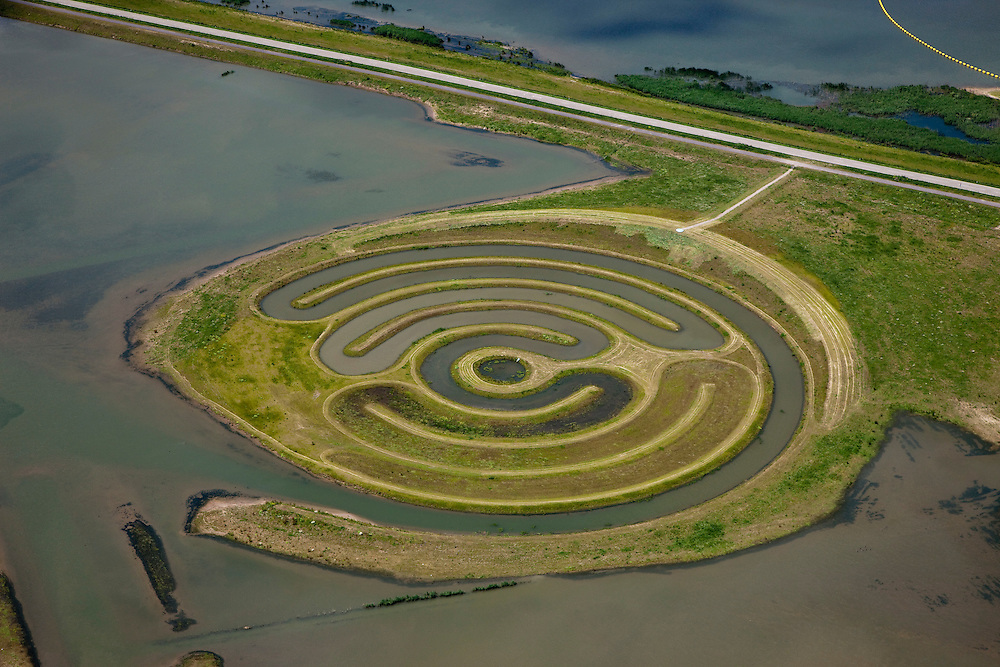 landschapskunstwerk De Wassende Maan van kunstenaar Paul de Kort: afhankelijk van het getij staan de spiralen van het labyrint meer of minder onder water. Het kunstwerk ligt in polder de Noordwaard in de Biesbosch. In het kader van Ruimte voor de Rivier' (bescherming tegen hoogwater door rivierverruiming) is de dijk van de Merwede gedeeltelijke afgraven (onder in beeld). Doel is het maken van een doorstroomgebied (naar rechtsboven),  bij hoge waterstanden zal het water van de Nieuwe Merwede afgeleid worden en zo westelijk naar het Hollandsch Diep afgevoerd worden. De kans op overstromingen (in de bovenloop) is hierdoor kleiner..Landart from artist Paul de Kort, Growing Moon: depending on the height of the tide, the spiral willl be more or less visible. The art work lies in Polder Noordwaard (part of Biesbosch National Park), part of the program 'Space for the River' (protection against high water by means of creating space for rivers). The former polder can store water and allows the river to flood more easily downstream. These measures dimishes the risk of floods further upstream at high water in the winter..Swart collectie, luchtfoto (25 procent toeslag); Swart Collection, aerial photo (additional fee required).foto Siebe Swart / photo Siebe Swart