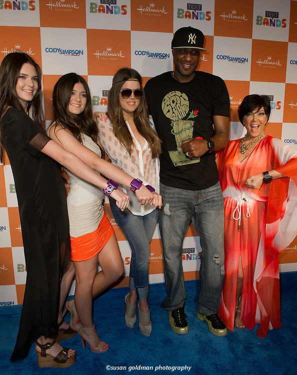 Khloe Kardashian, center, and husband Lamar Odom, join sisters Kendall Jenner, left, Kylie Jenner, and mom Kris Jenner, right, on the red carpet sporting Hallmark Text Bands, in Santa Monica, Calif. The family bumped fists to trade messages with fans during the Hallmark Text Band launch party. Photo/Hallmark, Susan Goldman.