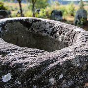 The top of a stone jar at Site 3 of the Plain of Jars in north-central Laos. Much remains unknown about the age and purpose of the thousands of stone jars clustered in the region. Most accounts date them to at least a couple of thousand years ago and theories have been put forward that they were used in burial rituals.